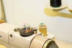 Needlework, выстегивающ, шьющ и портняжничающ концепцию - красочные штыри на магните на швейной машине, инструменты крупный план, стоковое фото