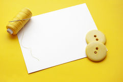 Needlework. Yellow thread, needles and some buttons on blank note Stock Photography