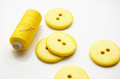 Needlework. Some yellow big buttons and thread Royalty Free Stock Images