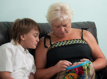 Needlework. An elderly woman embroiders her grandson sitting beside him stock photo