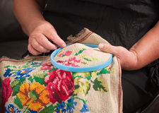 Needlework. The elderly woman is engaged in needlework, embroiders royalty free stock images