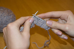 Needlework. Knitting of a product from a wool spokes manually Stock Image