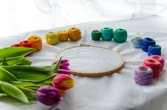 Needlework accessories. Colorfull needlework accessories on white background and bouquet of tulips Royalty Free Stock Image