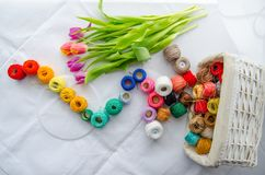 Needlework accessories. Colorfull needlework accessories on white background and bouquet of tulips Stock Images