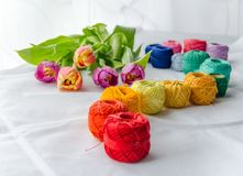 Needlework accessories. Colorfull needlework accessories on white background and bouquet of tulips Stock Photos