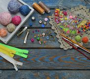 Needlework accessories for creating crocheted jewelry. Beads, threads, hooks, buttons on wooden background. Knitting, crochet, emb. Roidery, sewing Small Stock Photo