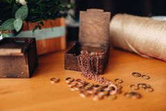 Needlework, metal rings and wooden box on table. Needlework accessories, little metal rings and decorative wooden box on the table, closeup. Handmade jewelry Stock Photo