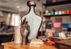 Needlework accessories, wooden hand and mannequin. On the table, closeup. Handmade jewelry, workshop interior Stock Photo