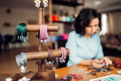 Needlework tools, master at workplace in workshop. Needlework, box with accessories, bracelets, female master at workplace in workshop on background. Handicraft Stock Photos