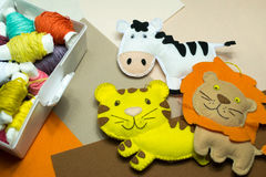 Needlework. Box with colored threads and handmade soft toys. Box with colored threads. Background neutral shades. Handmade soft toy tiger, zebra, lion Royalty Free Stock Image
