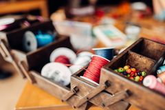 Needlework, box with ropes, beads and accessories. Needlework, box with colorful ropes, beads and accessories on wooden table, nobody. Handicraft tools. Handmade Stock Photography