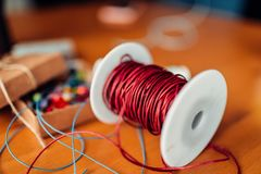Needlework, coil with red decorative rope, closeup. Box with colorful beads, accessories on wooden table, nobody. Handicraft tools. Handmade accessories Stock Photography