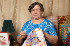 Needlework. Embroidery. The elderly woman is engaged in needlework, embroiders Royalty Free Stock Photography