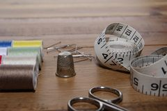 Needlework essentials on a wooden sewing table.  Stock Images