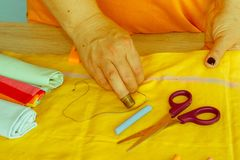 Needlework and hand quilting in the workshop of a tailor woman -. On the desktop of thread, scissors. female in costume sewing Stock Photo