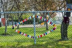 Needlework hanged on a fence. In a public park on a sunny day Royalty Free Stock Photo
