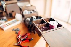 Needlework hobby, handicraft tools, closeup. Workplace of a craftsman, handmade bijouterie Stock Photos