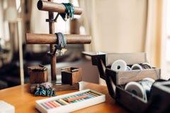 Needlework hobby, handmade bracelets, bijouterie. Needlework hobby, handicraft tools, closeup. Equipment of a craftsman, handmade bracelets and bijouterie Stock Images