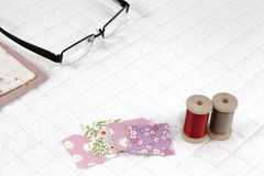 Needlework put on white patchwork Quilt background Royalty Free Stock Photos