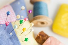 Needlework, quilting, sewing and tailoring concept - colorful cute stitched pincushion with lot of beautiful pins, tools. Closeup on white desk, blue and pink Stock Photos