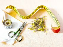 Sewing centimeter, scissors, pins, fabric Royalty Free Stock Images
