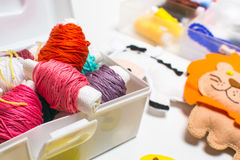 Needlework. Sewing kits with colored thread and handmade soft toys. Sewing kit with colored thread and handmade soft toy tiger, zebra, lion Royalty Free Stock Images