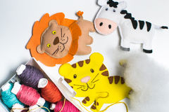 Needlework. Sewing kits with colored thread and handmade soft toys. Sewing kit with colored thread and handmade soft toy tiger, zebra, lion Royalty Free Stock Image