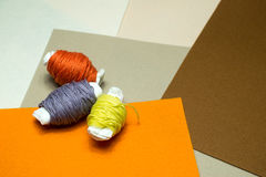 Needlework. Sewing kits with colored thread. Three skein of thread on a background of neutral tones Royalty Free Stock Photos