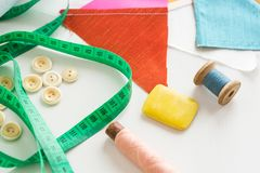 Needlework, sewing and tailoring concept - close-up on green measuring meter, white buttons, blue and pink thread in the Stock Photo