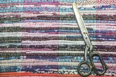 Needlework. Textile background with fabric texture with horizontal lines. Vintage dressmaker`s scissors and home mat made from