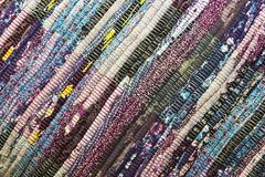 Needlework. Textile fabric background with diagonal lines. Rug for home made from colorful patches of old things sewn in rows stock image