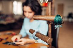Needlework tools, master at workplace in workshop. Needlework, box with accessories, bracelets, female master at workplace in workshop on background. Handicraft Royalty Free Stock Photos