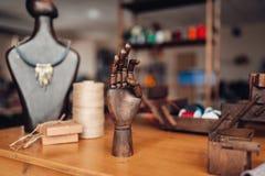 Needlework tools on table in workshop, bijouterie. Needlework accessories, wooden hand and mannequin with handmade bijouterie on the table in workshop, closeup Stock Photos