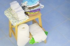 Needs for babies: cloth diapers, nappy liners, changing pad are prepared on wooden stool. Stock Photography