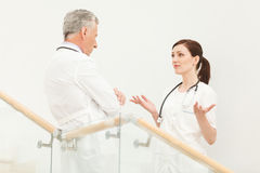 She needs a professional advice. Mature doctor listening to his Stock Photos