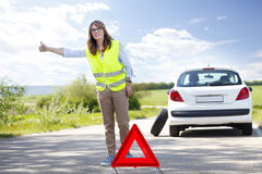 She needs some help. Portrait of middle aged woman standing on the side of the road besides her car and hitching a ride royalty free stock photo