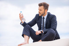 He needs to get refreshed. Depressed young businessman holding bottle with water and looking at it while sitting on sand Royalty Free Stock Photos
