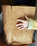 Needy Hands at Food Pantry. Old woman receives paper sack of groceries at food pantry. Her hand is wrinkled and reaches to lift paper sack royalty free stock images