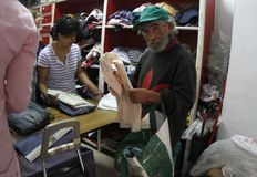 Needy man at charity clothing center in mallorca. A man receives some charity clothes on a volunteer support for homeless or needed center in Palma de Mallorca Stock Photography