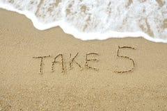 Neem 5 geschreven op zand royalty-vrije stock afbeeldingen