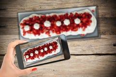 Neem smartphonebeeld van een perfecte Pavlova-cake met schuimgebakje, room en aardbeien Royalty-vrije Stock Foto