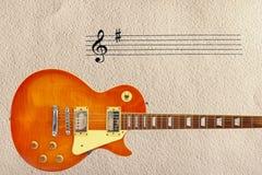 Neemt nota staaf en honingszonnestraal van uitstekende elektrische gitaar bij de bodem van ruwe kartonachtergrond Stock Fotografie