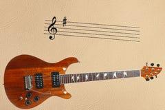 Neemt nota van staaf en exotische houten elektrische gitaar bij de bodem van lichte huidachtergrond Stock Fotografie