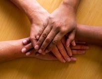 Neer kijkend op vier die handen ontop van elkaar, hoogste h worden geplaatst Stock Afbeelding