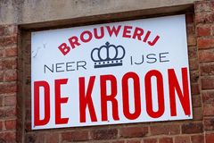 NEERIJSE, BELGIUM - SEPTEMBER 05, 2014: Signboard of the family brewery De Kroon in Neerijse on the old red brick wall. royalty free stock photo