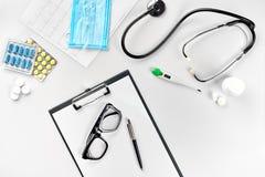 Negócio ajustado para o hospital: comprimidos, estetoscópio, equipamento médico, livro de nota com pena e vidros no fundo branco Fotos de Stock