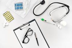 Negócio ajustado para o hospital: comprimidos, estetoscópio, equipamento médico, livro de nota com pena e vidros no fundo branco Imagem de Stock Royalty Free