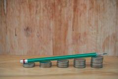 Negócio criativo e conceito da ideia: Lápis verde usado na pilha de baht das moedas de prata posto sobre a tabela de madeira Imagens de Stock Royalty Free