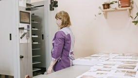 Negócio da tipografia - mulher que trabalha na máquina do dobrador na casa de impressão - indústria do polígrafo filme