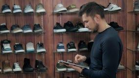Negócio de Running Online Shoe do homem de negócios com a tabuleta de Digitas, estando na loja extrema da sapatilha video estoque
